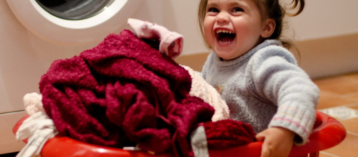 Portrait of an adorable little girl smiling in a red laundry basket with towels.