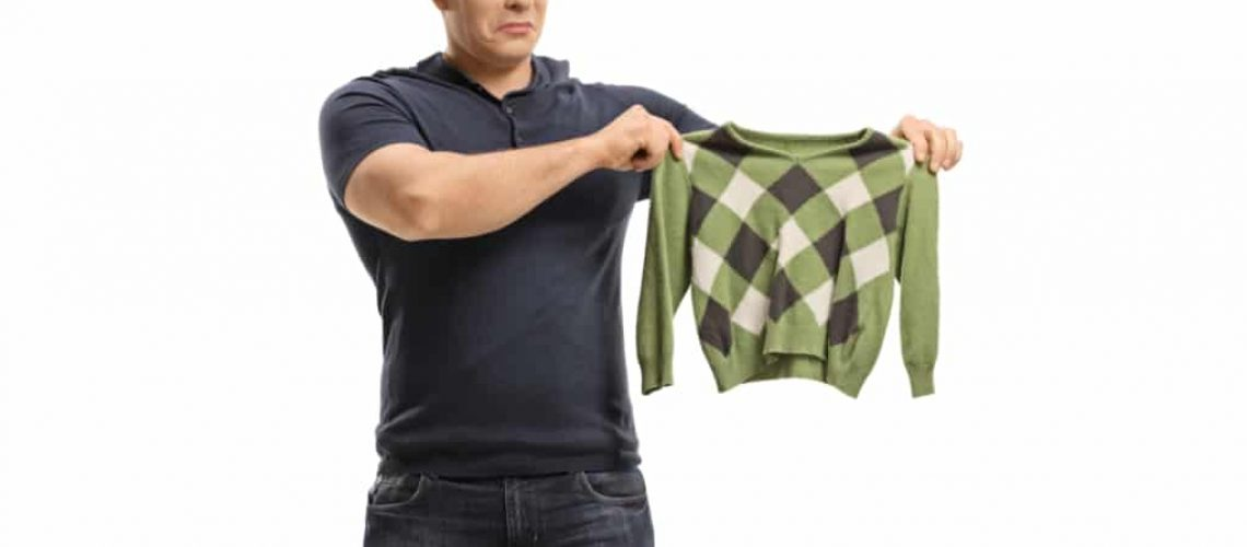 Upset young man with a shrunken blouse isolated on white background